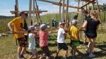 Mehrere Teilnehmer der Gruppe beim gemeinsamen Transportieren einer Holzkonstruktion