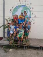 Gruppenfoto einiger Kinder vor einem Wandbild, welches einen Globus zeigt