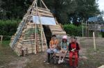 drei Kinder sitzen auf deiner Bank vor einer Pyramide aus Holz