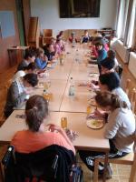 Das Essen ist serviert. Alles sitzen gemeinsam an einem langen Tisch und lassen es sich schmecken