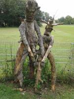Skulptur zweier Personen aus Baumstämmen und Ästen