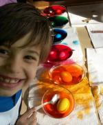 Ein Junge grinst beim Bemalen der Ostereier frech in die Kamera