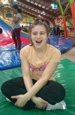 Eine fröhlich lachende junge Dame beim Spielen auf einer Matte