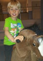 EIn Junge reitet auf einem Spielzeug-Pferd