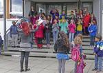 Gruppenfoto des Projektchors beim Singen auf der Treppe vor der Grundschule Unterlauchringen