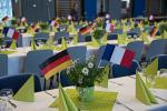 Die Tische sind festlich geschmückt, mit hellgrünen Servietten und Dekorationen sowie den Flaggen von Frankreich und Deutschland