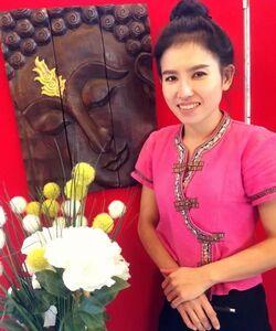 Chuan Chom Massage - Mitarbeiterin Nut in traditioneller thailaendischer Tracht
